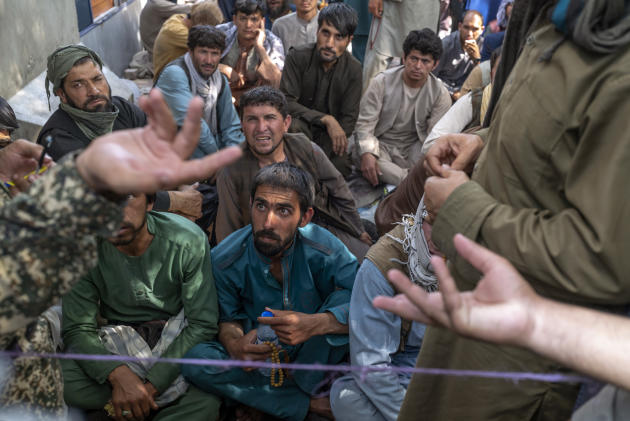 Men have been waiting since morning, some for several days, in front of the New Kabul Bank, September 14, 2021, in Kabul.